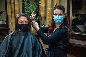 Hairdresser and customer wearing masks