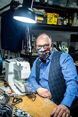 Man wearing mask at sewing machine