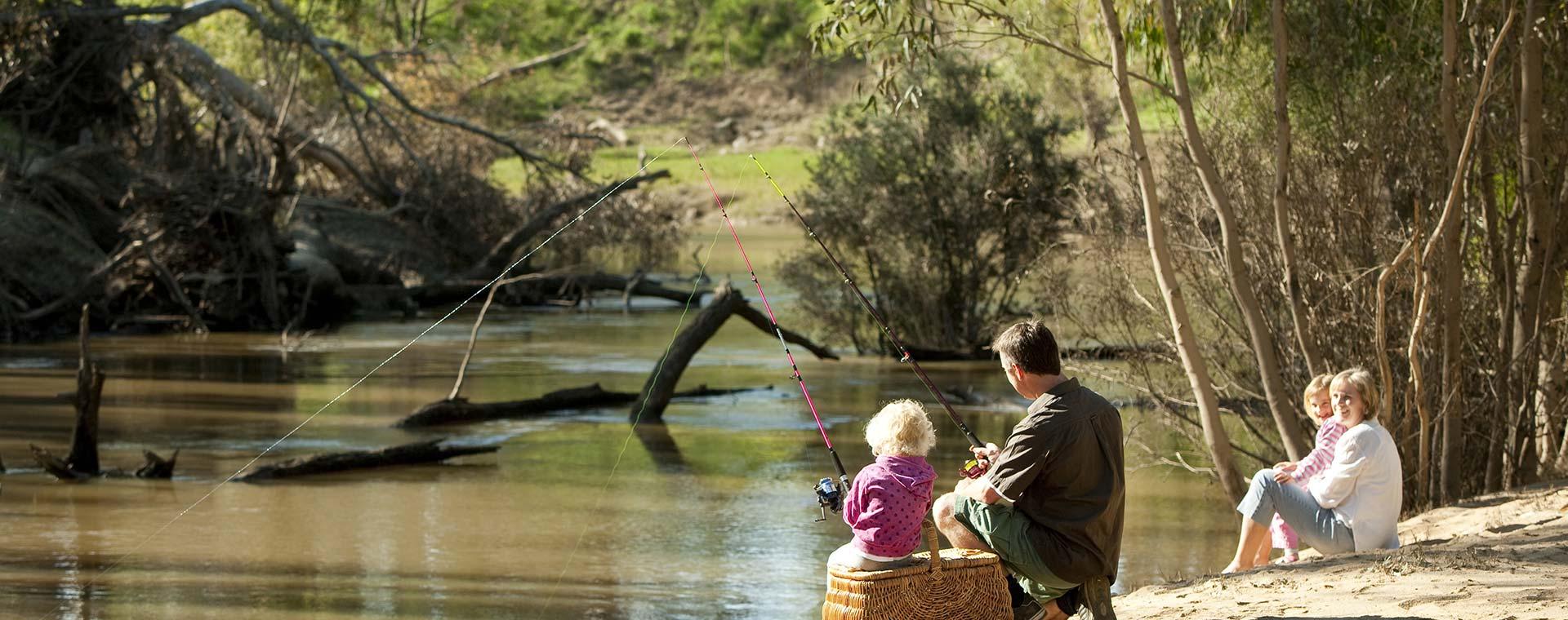 Family enjoying a fishing picnic by the river.