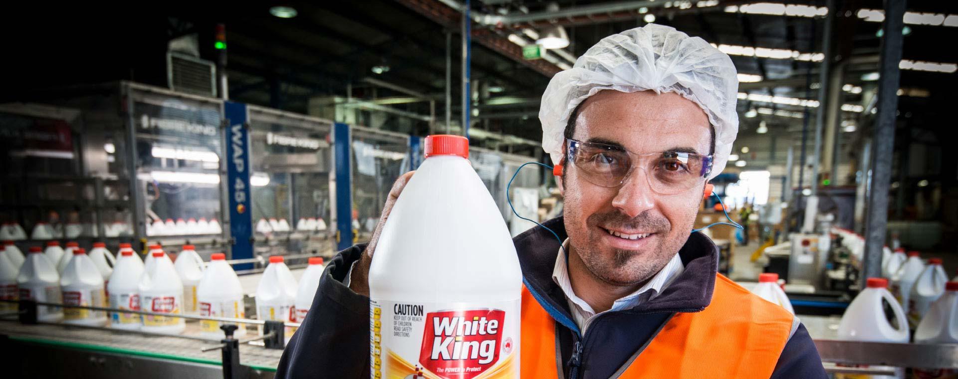 Pental worker holding up bottle of White King